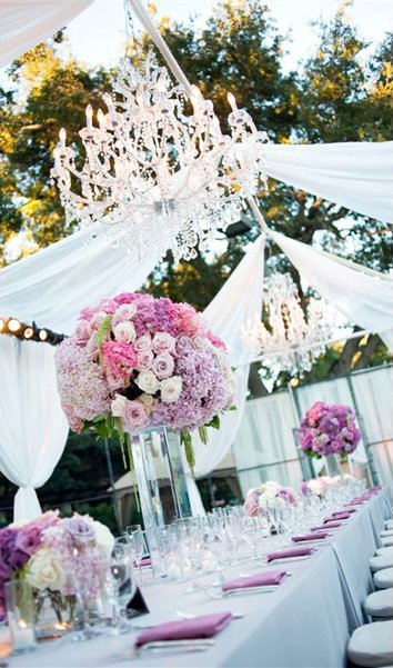 Ourdoor drapped wedding reception with purple floral and crystal chandelier